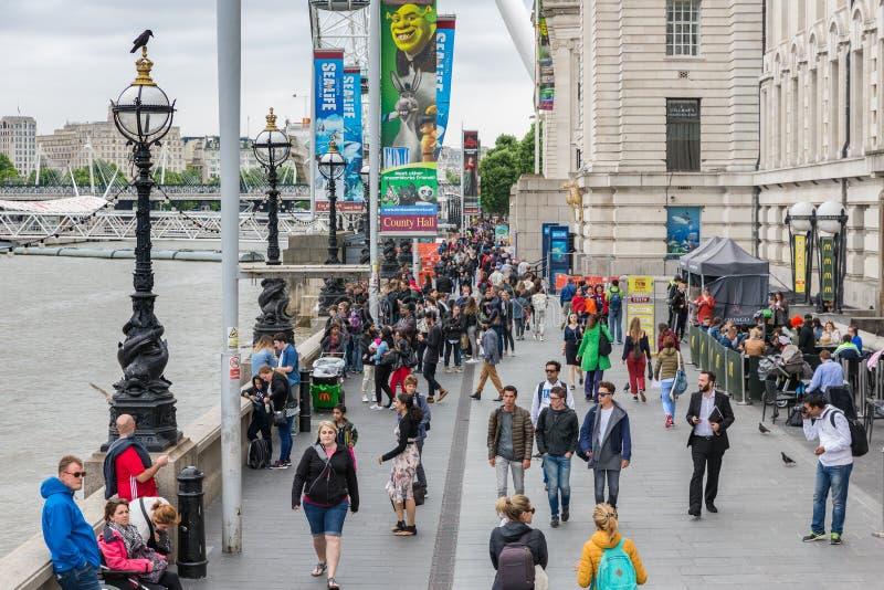 Leute an der Promenade zwischen London-Auge und Westminster-Brücke, L stockfotos
