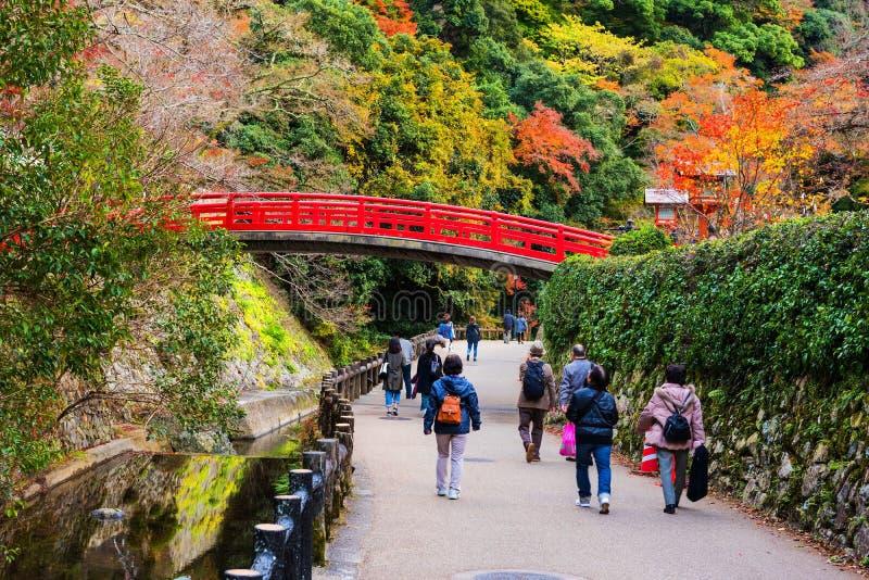 Leute an der roten Brücke, Minoo-Wasserfall, Osaka lizenzfreie stockfotografie
