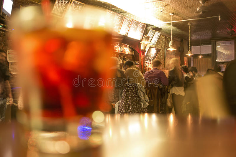 Leute an der Tauchenbar mit einem Manhattan-Cocktail im Vordergrund lizenzfreies stockfoto