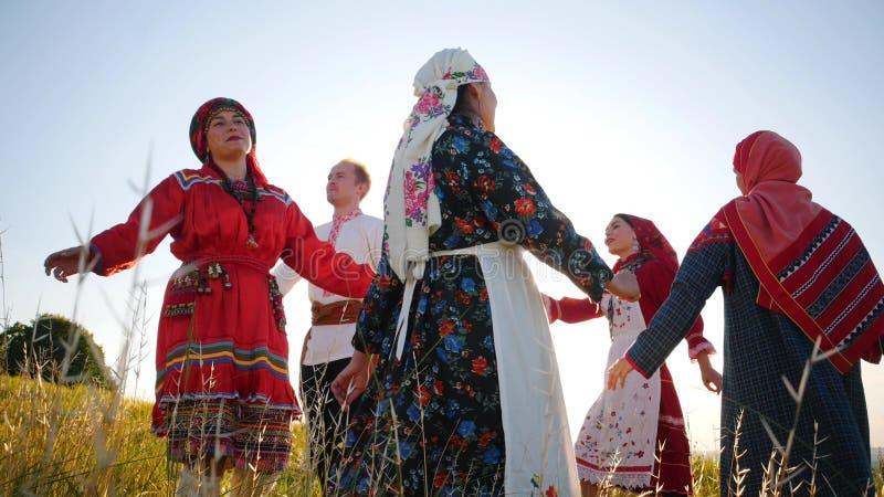 Leute in der traditionellen russischen Kleidung, die einen runden Tanz auf dem Feld durchführt stockfotografie