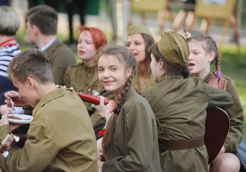 Leute in der Uniform der russischen Soldaten von Zeiten des Zweiten Weltkrieges essen zu Abend und haben einen Rest lizenzfreie stockbilder