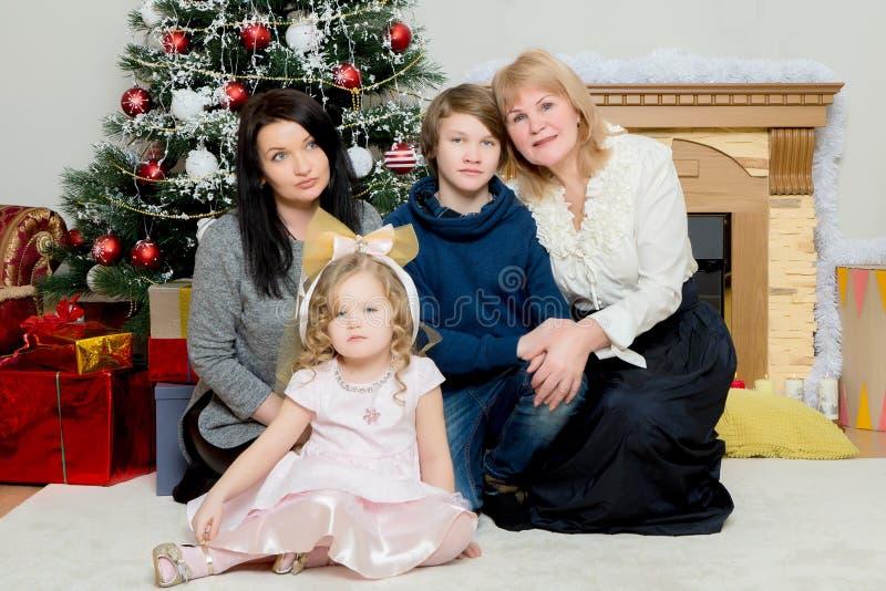 Leute der vierköpfigen Familie um einen Weihnachtsbaum lizenzfreie stockbilder