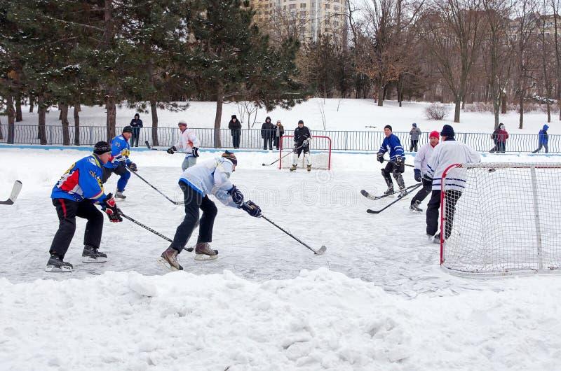 Leute, die Amateurhockey in der Stadt Eislaufeisbahn spielen Winter spielend, Spaß, Schnee lizenzfreie stockfotos