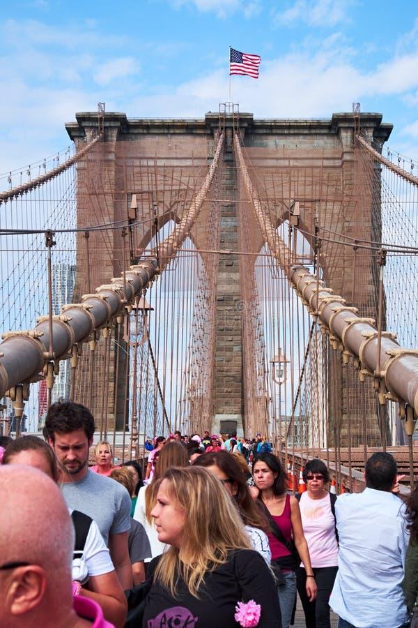 Leute, die auf Brooklyn-Brücke marschieren stockbild