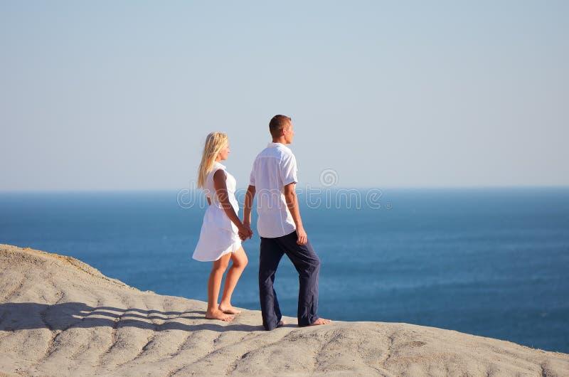 Leute, die auf dem Hügel und den Blicken in dem Meer stehen lizenzfreies stockbild