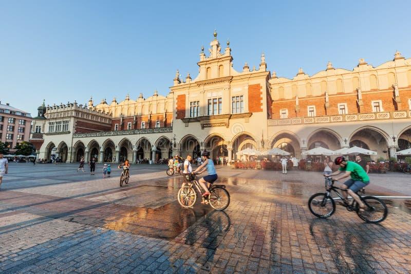 Leute, die auf den Hauptmarktplatz von Krakau, Polen radfahren stockfotografie