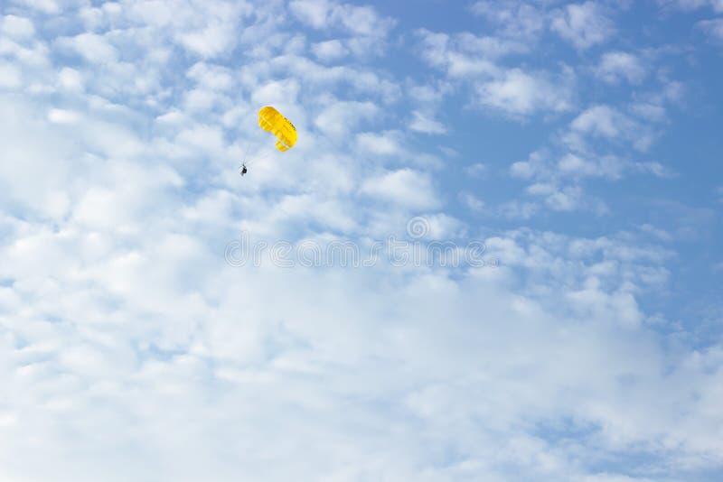 Leute, die auf einen gelben Fallschirm im Himmel fliegen stockbilder