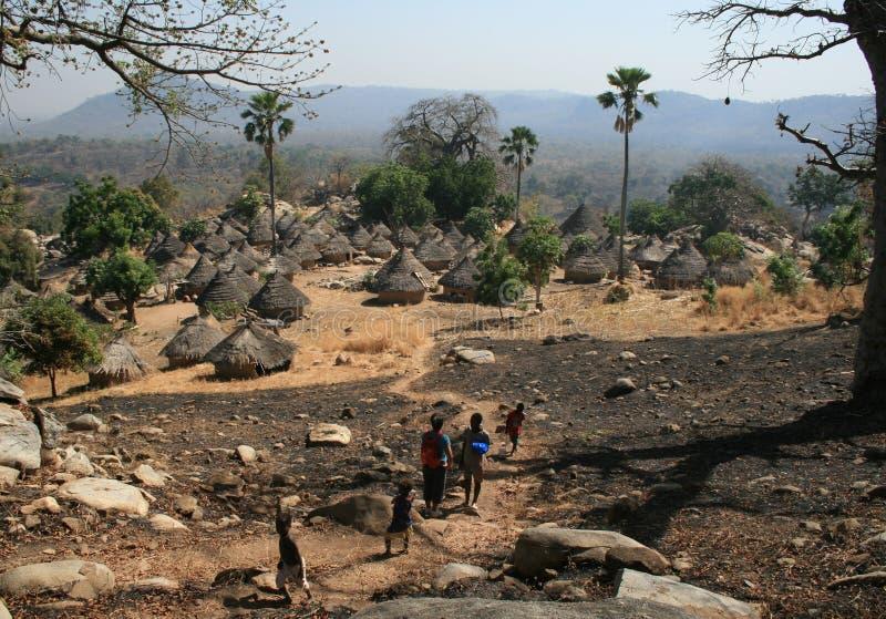 Leute, die auf einen Weg gehen und ein kleines ländliches Dorf von Kedougou-Region in Senegal entdecken lizenzfreie stockfotografie