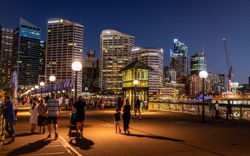 Leute, die auf Pyrmont-Brücke nachts mit Ansicht über den Steuerkabinenturm in der Mitte der Drehbrücke in Sydney Australia gehen lizenzfreie stockfotografie