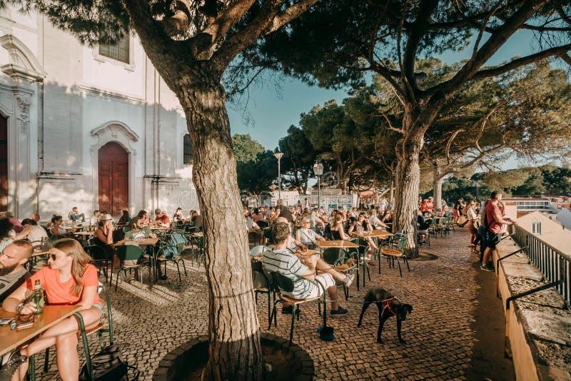 Leute, die auf Restaurantterrasse mit Stadtansicht unter enormen grünen Bäumen trinken und sich entspannen lizenzfreies stockbild