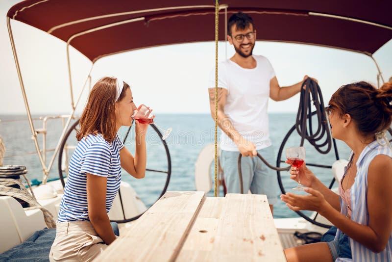 Leute, die auf Segelbootplattform sitzen und Spaß haben Ferien, Reise, Meer, Freundschaft und Leutekonzept lizenzfreies stockbild