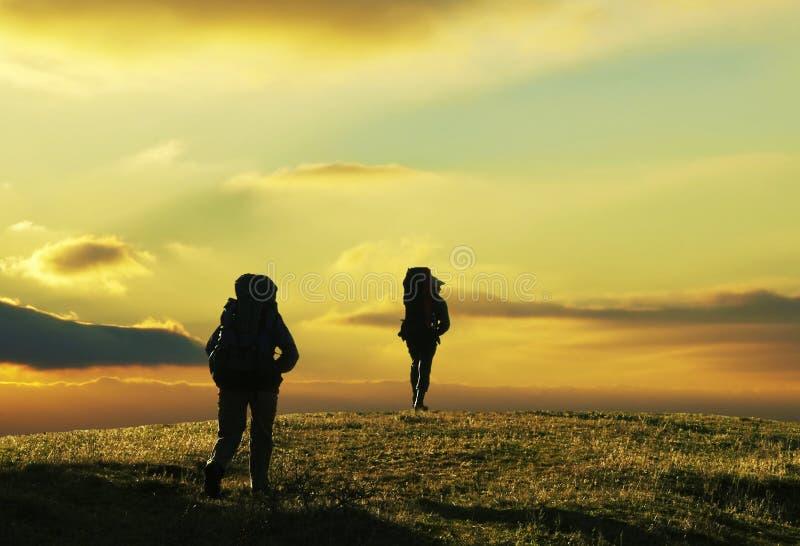 Leute, die auf Sonnenuntergang im Trekking gehen lizenzfreie stockfotografie