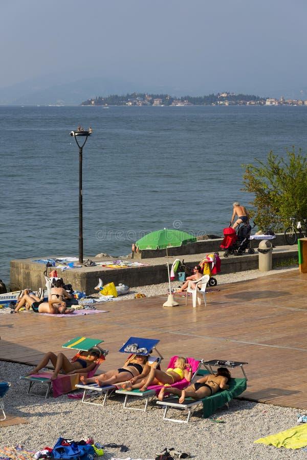 Leute, die auf Strand am 30. Juli 2016 in Desenzano del Garda, Italien ein Sonnenbad nehmen lizenzfreie stockfotografie