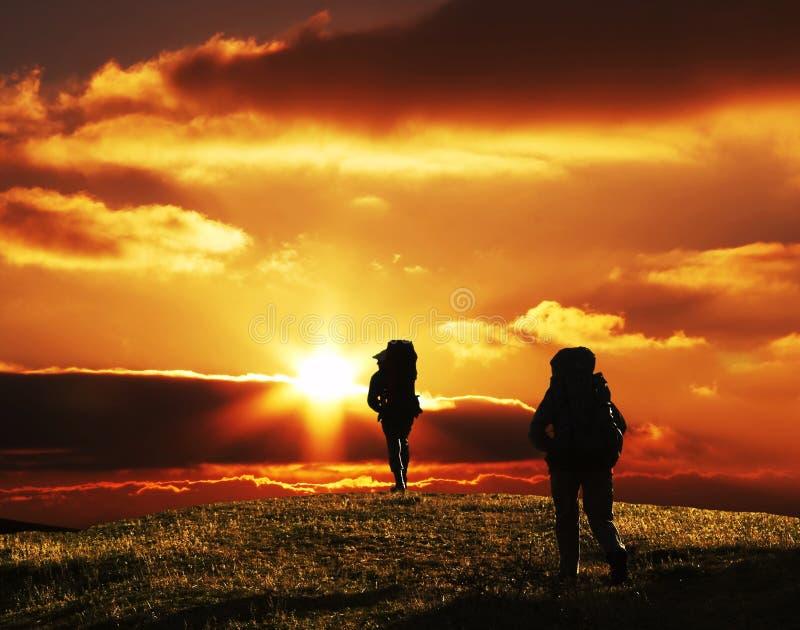 Leute, die auf suset im Trekking gehen lizenzfreie stockfotografie