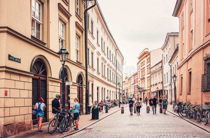 Leute, die auf verkehrsreiche Straße in der alten Stadt Krakau gehen und radfahren stockbild