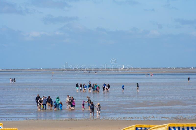 Leute, die bei Ebbe auf den Strand in Cuxhaven gehen Leute im Wasser auf der Nordsee stockfotos