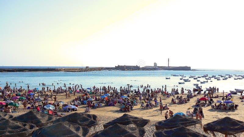Leute, die bei Sonnenuntergang auf dem Strand von La Caleta in der Bucht von Cadiz, Andalusien ein Sonnenbad nehmen spanien lizenzfreie stockfotografie