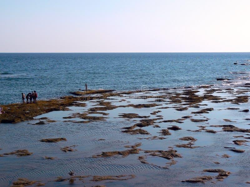 Leute, die bei Sonnenuntergang auf dem Strand von La Caleta in der Bucht von Cadiz, Andalusien ein Sonnenbad nehmen spanien lizenzfreies stockbild