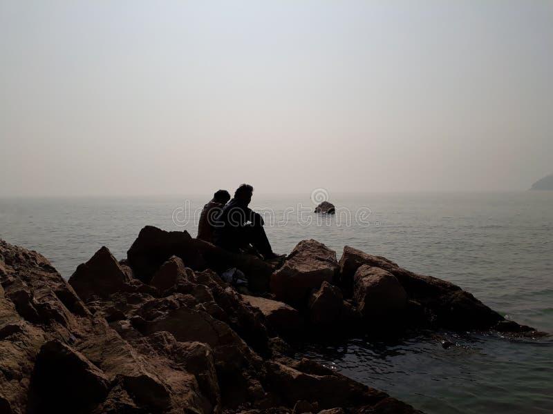 Leute, die das Sitzen auf den Felsen am Seestrand sitzen und genießen stockfoto