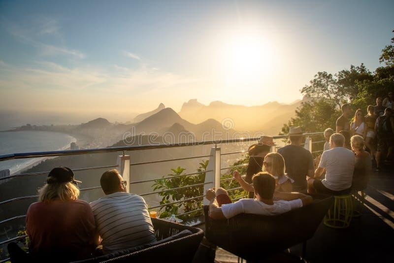 Leute, die den Sonnenuntergang über Rio de Janeiro von Sugar Loaf Mountain - Rio de Janeiro, Brasilien aufpassen stockfoto