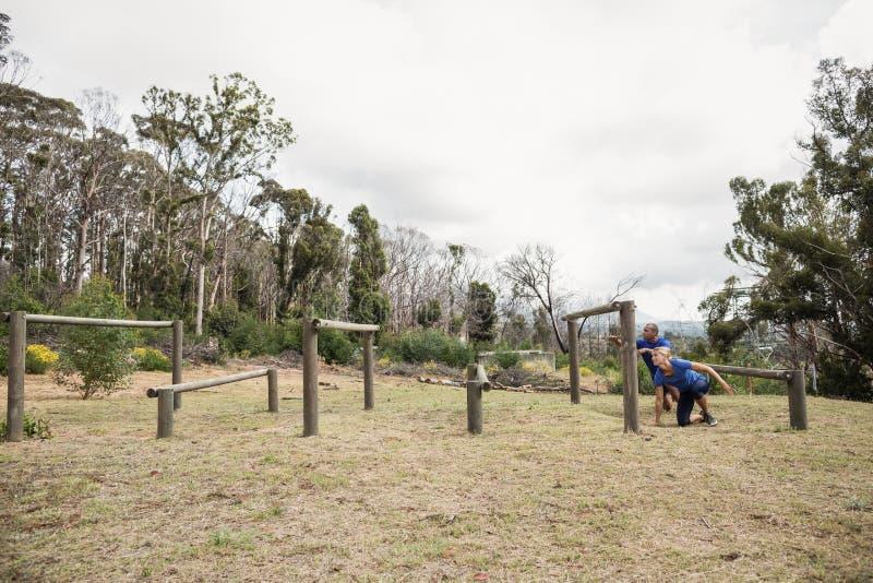 Leute, die durch Hürden während des Hindernislaufs überschreiten lizenzfreies stockbild