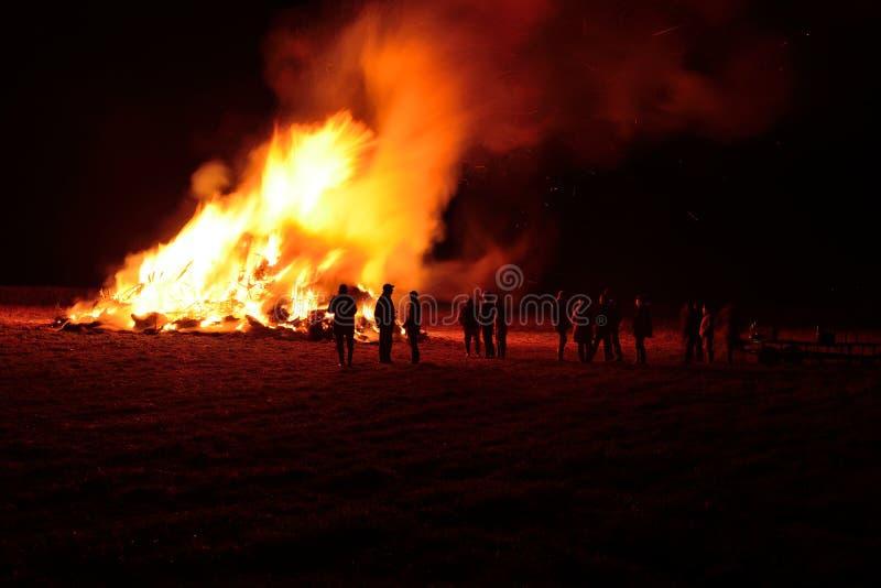 Leute, die ein Feuer aufpassen, nachts zu brennen lizenzfreie stockfotografie