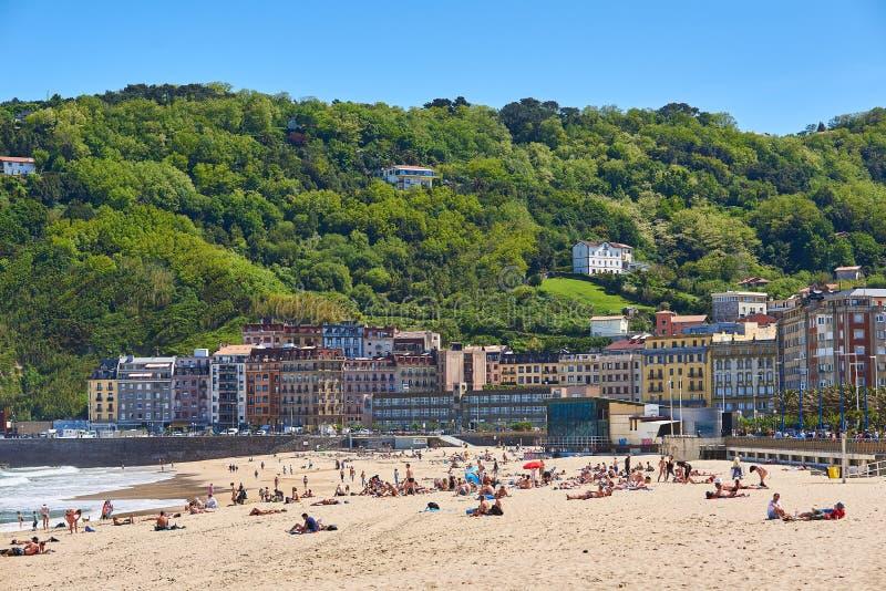 Leute, die ein Ein Sonnenbad nehmen in Zurriola-Strand von San Sebastián genießen lizenzfreie stockbilder