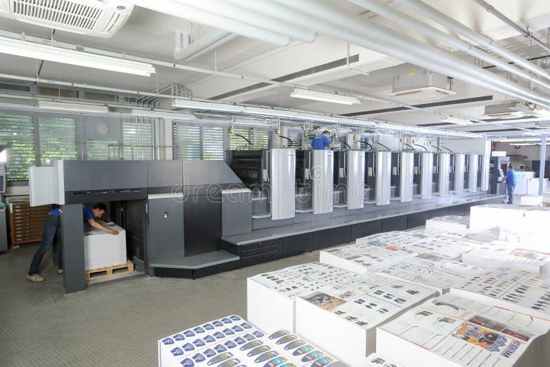 Leute, die an einer Offsetdruckmaschine arbeiten stockfotos