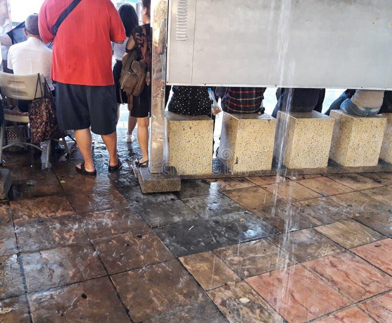 Leute, die für den Bus erwarten, während der Regen noch unten an der Ecke des Siegmonuments in Thailand fällt lizenzfreies stockbild
