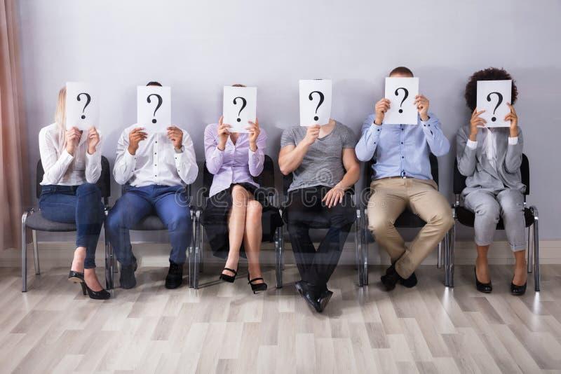 Leute, die Frage Mark Sign halten stockbild