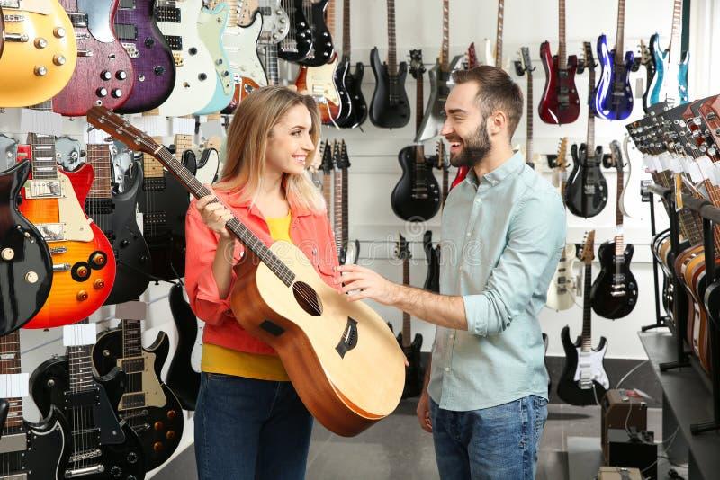 Leute, die Gitarre im Musikspeicher w?hlen stockfotos