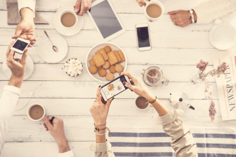 Leute, die gute Zeit auf weißem Holztisch haben lizenzfreie stockbilder