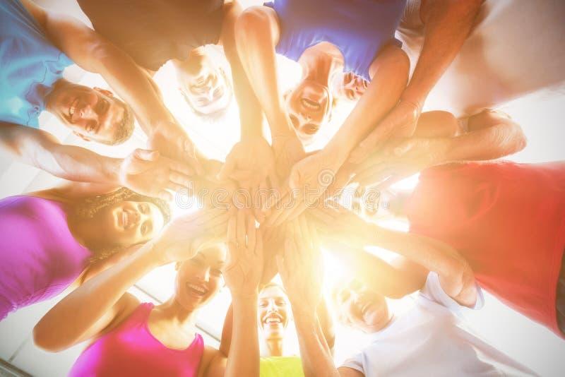 Leute, die Hände am Fitnessstudio stapeln lizenzfreies stockbild