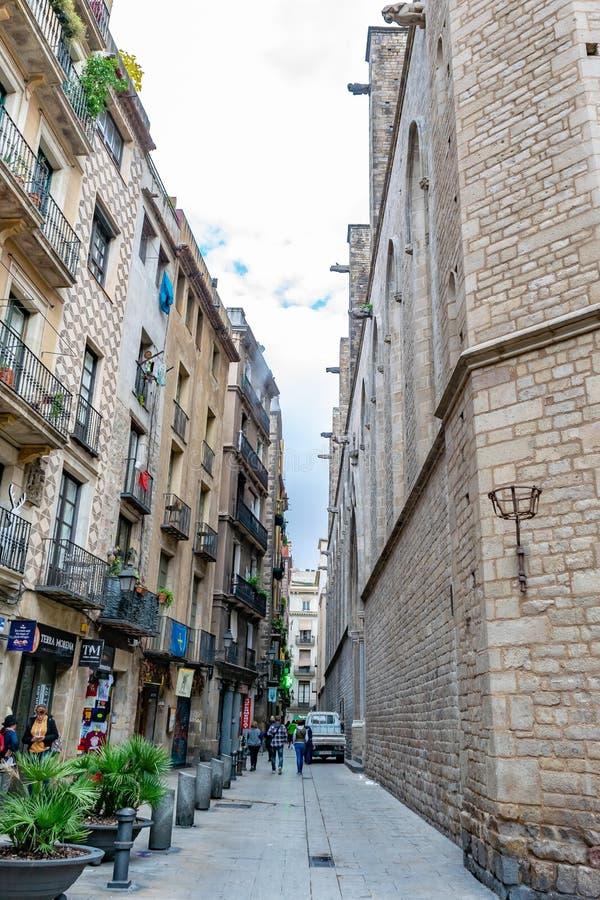Leute, die hinunter eine Gasse/eine schmale Stra?e in einem Bereich von Wohn- und gewerblich gen?tzten Grundbesitzen in Barcelona lizenzfreie stockfotografie