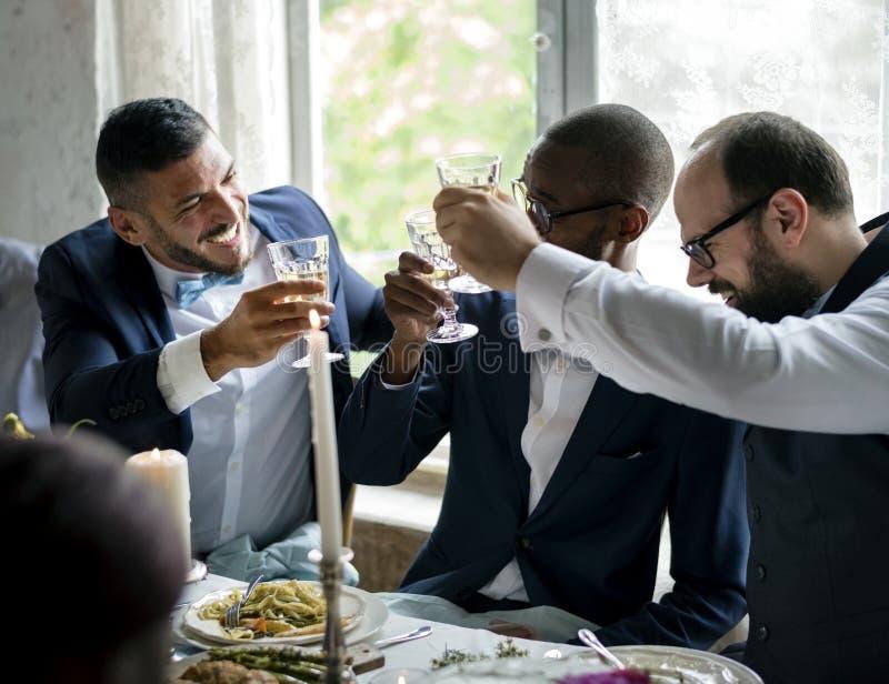 Leute, die ihre Champagnergläser für einen Toast an einer Hochzeitstafel halten lizenzfreies stockfoto