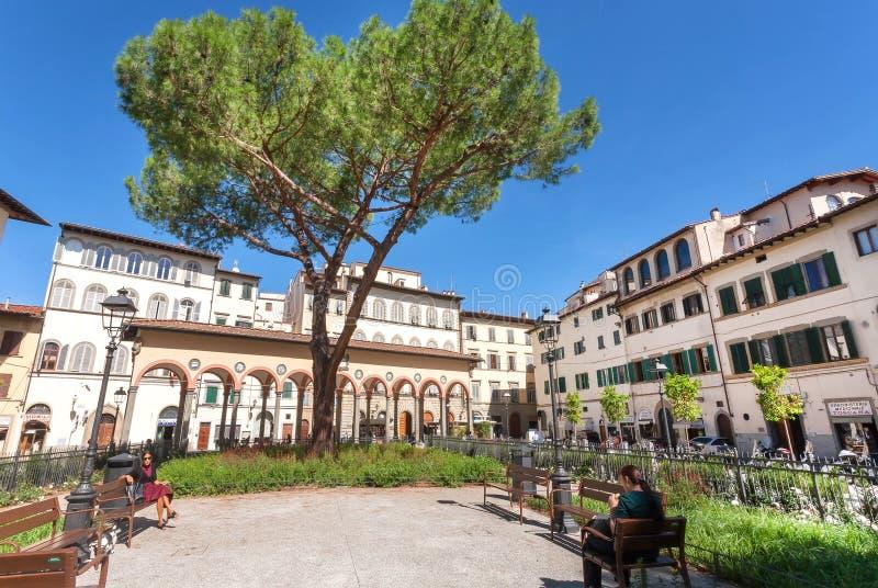 Leute, die im kleinen grünen Park in der Mitte historischer Toskana-Stadt sich entspannen stockfoto