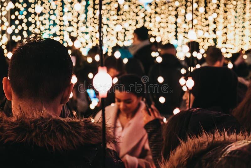 Leute, die innerhalb der Winter-Lichter, Canary Wharf, London, Großbritannien gehen lizenzfreie stockbilder
