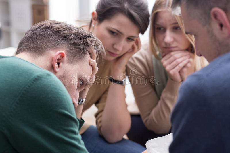 Leute, die jungen Mann während der Gruppentherapiesitzung trösten stockfotos