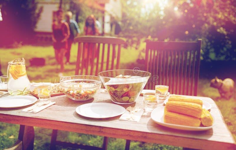 Leute, die kommen, mit Lebensmittel am Sommergarten zu verlegen lizenzfreies stockbild