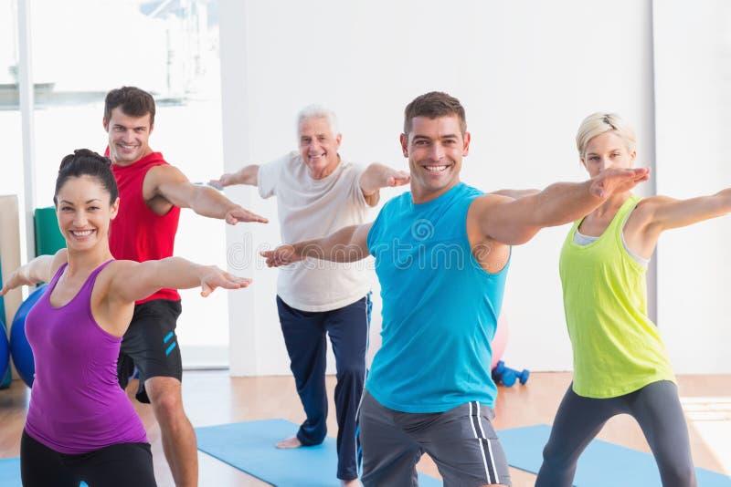 Leute, die Kriegershaltung in der Yogaklasse tun lizenzfreie stockfotos
