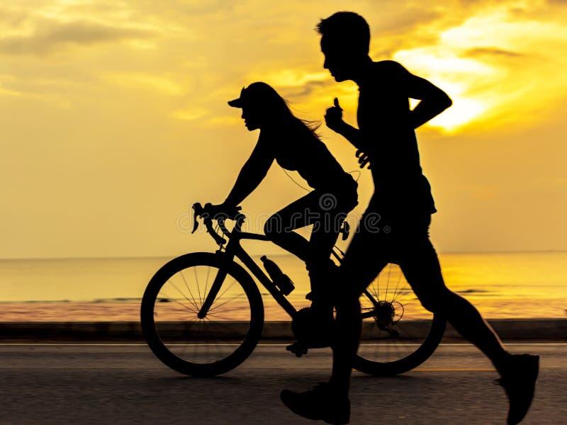 Leute, die laufen gelassen werden und am Strand Rad gefahren sind lizenzfreies stockbild