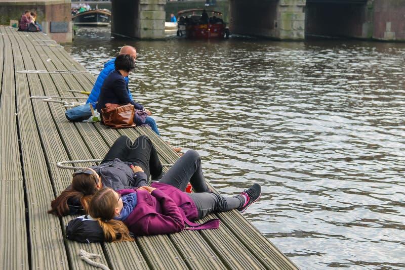 Leute, die am Liegeplatz nahe dem Wasser in Amsterdam stillstehen stockfoto