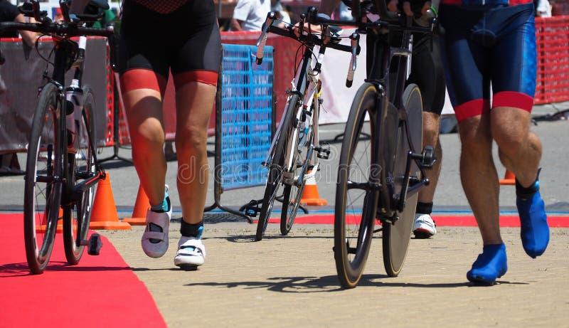 Leute, die mit Fahrrädern in der Triathlonmeisterschaft laufen stockfoto