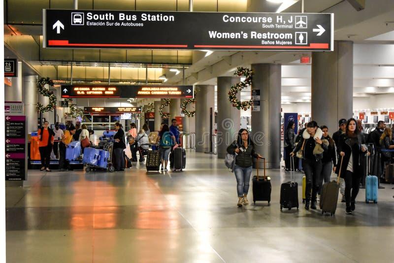 Leute, die mit Koffern und Südbusbahnhofzeichen an internationalem Flughafen Miamis gehen lizenzfreie stockfotografie