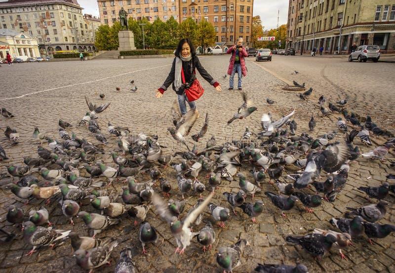 Leute, die mit Menge von Tauben in einem Quadrat spielen lizenzfreie stockbilder
