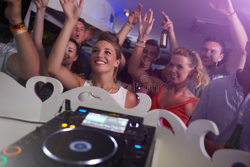 Leute, die in Nachtklub mit DJ im Vordergrund tanzen lizenzfreies stockfoto