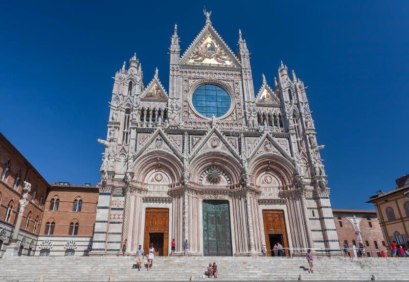Leute, die nahe dem Tor der Duomodi des 14. Jahrhunderts Siena am hellen sonnigen Tag gehen lizenzfreie stockfotos