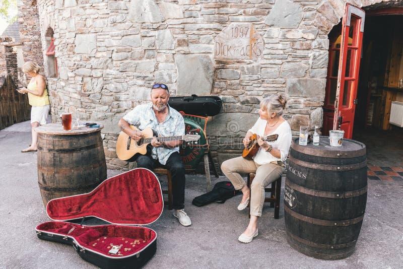 Leute, die nahe den Kneipen in der kleinen Hafenstadt auf dem Südwesten der Irland-Dingle-Halbinsel busking sind lizenzfreie stockfotos