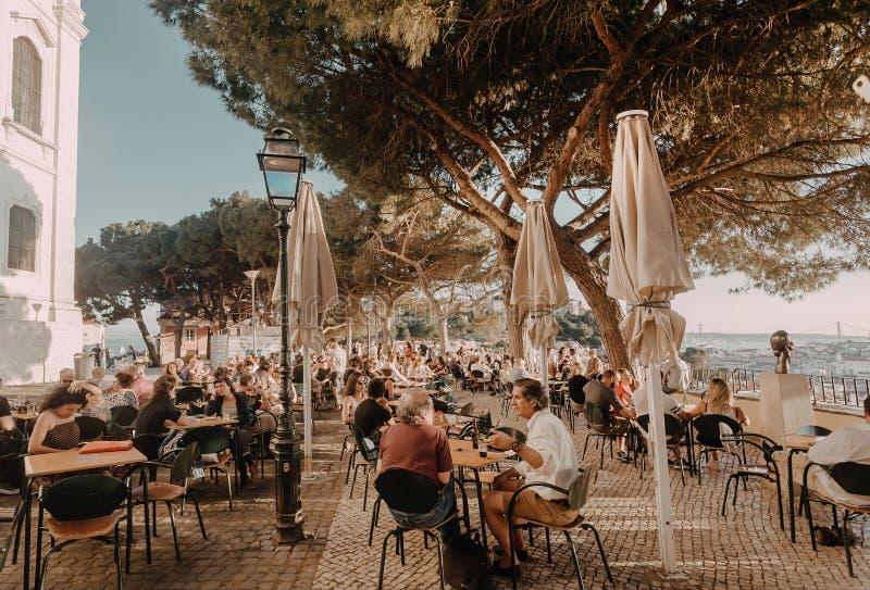 Leute, die Nahrung auf Restaurantterrasse mit Stadtansicht unter enormen grünen Bäumen trinken und essen stockfoto
