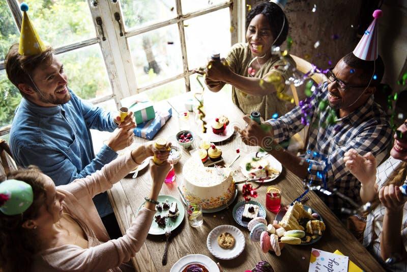 Leute, die Partei verwenden, knallend auf Freund-Geburtstags-Feier lizenzfreies stockfoto